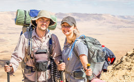 Backpackers туристов пар стоя гребень горного пика пустыни Стоковые Изображения