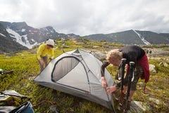 Backpackers устанавливают шатер в горах Стоковые Изображения RF
