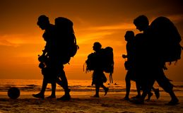 Backpackers on the beach. Backpackers silhouette on a sunset beach stock photos