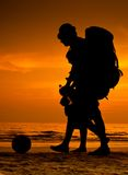 Backpackers on the beach. Backpackers silhouette on a sunset beach stock photo