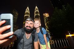Backpackers in a big city. Father and son happy and excited together for the Malaysia trip. Having fun, taking selfies. Holidays. Backpackers in a big city Stock Image