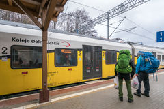 Backpackers boarding the train. Two backpacking tourists boarding ready to depart local train operated by Koleje Dolnoslaskie company standing on a platform on Royalty Free Stock Images