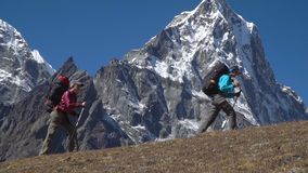 Backpackers climb in the mountains stock footage