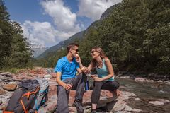 Backpackers couple lunch break with landjaeger and bread on a river royalty free stock photo