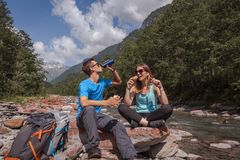 Backpackers couple lunch break with landjaeger and bread on a river royalty free stock photos