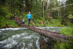 Backpackers are crossing mountain river Stock Photography