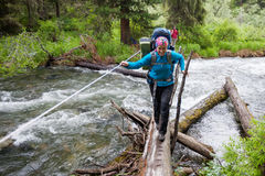 Backpackers are crossing mountain river Royalty Free Stock Image