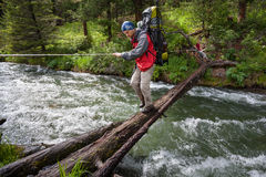Backpackers are crossing mountain river Stock Photo