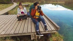 Backpackers de las mujeres que se sientan en la trayectoria de madera metrajes