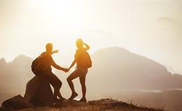 Backpackers de los pares en el top de la montaña en la puesta del sol Fotos de archivo libres de regalías