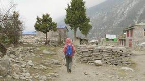 Backpackers die in het Nepalese dorp lopen Trek van de Manaslukring gebied stock videobeelden