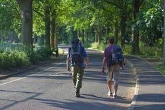 Backpackers die langs weg loopt Stock Foto
