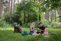 Backpackers family dining in nature Stock Images