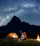 Backpackers girl and guy looking at the shines starry sky at night. Young couple sitting near tent and campfire Stock Photos