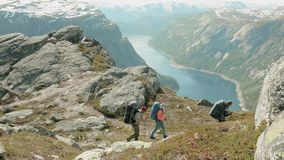 Backpackers go to the Trolltunga in Norway.  stock video