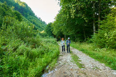 Backpackers hiking into the mountains Royalty Free Stock Images