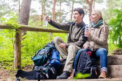 Backpackers taking rest and having mineral water. Backpackers hiking and taking rest in the woods and having mineral water royalty free stock photography