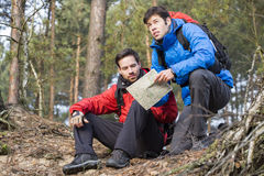 Backpackers with map in forest Stock Photography