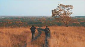 Backpackers masculinos que caminan en aventura de la montaña El viaje de los pares del caminante disfruta de paisaje escénico de  metrajes
