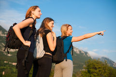 Backpackers in nature. Three cute girls on a hike in nature - three women with backpacks on a trip Royalty Free Stock Image