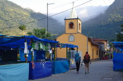 Backpackers passing market stalls. In a small town square of Vila do Abraao on Ilha Grande in Brazil royalty free stock images