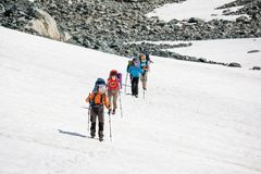 Backpackers are passing snow field in rocky mountain in Altai mo Royalty Free Stock Images