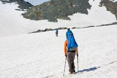 Backpackers are passing snow field in rocky mountain in Altai mo Stock Photo