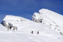 Backpackers que suben una montaña en invierno Fotos de archivo libres de regalías