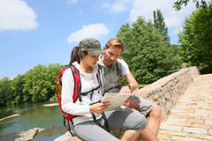 Backpackers reading map on the stone bridge Royalty Free Stock Images