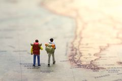 Backpackers standing on vintage world map stock image