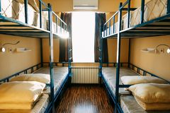 Backpackers stay in hotel with modern double-decker beds inside the dorm room for twelve people stock images