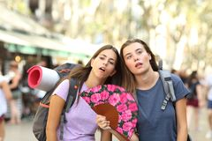 Backpackers suffering heat stroke on vacation. Two overwhelmed backpackers suffering heat stroke on summer vacation in the street stock photos