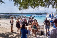 Backpackers waiting to embark the speedboat to Bali. Gili Trawngan, Indonesia, April 26, 2018 stock photography