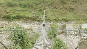 Backpackers walk on suspension bridge over river in Nepal. Manaslu circuit trek. Backpackers walk on suspension bridge over the river between high mountains in stock video