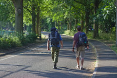 Backpackers walking along avenue Stock Photo