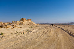 Backpackers walking desert road. Royalty Free Stock Image
