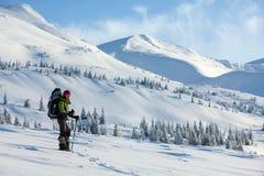 Backpackervrouw het stellen in de winterbergen Stock Afbeelding