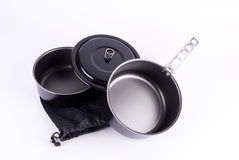 Backpacking cookware on white. Set of lightweight, non-stick backpacking style cookware with two pots, one lid, handle and mesh bag Royalty Free Stock Image