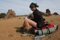 Backpacking in the desert. Woman sitting on big backpack reading the map Stock Images