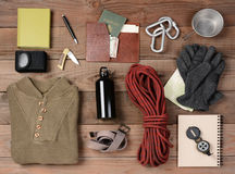 Backpacking Gear. Overhead view of gear laid out for a backpacking trip on a rustic wood floor. Items include, rope, gloves, sweater, carabineers book, belt, cup royalty free stock images