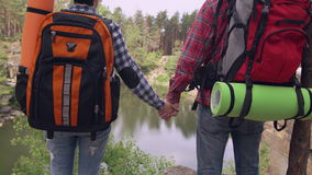 Backpacking people without face. Unrecognizable woman and man holding hands in canyon. Couple in love hiking with backpack enjoy beautiful landscape lake and stock footage