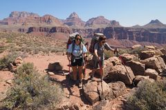 Backpacking sisters on the Tonto Trail in the Grand Canyon. Backpacking sisters on the Tonto Trail during a multi-day hike in Grand Canyon National Park stock photography