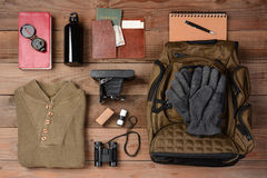 Backpacking Trip. Overhead view of gear laid out for a backpacking trip on a rustic wood floor. Items include, Backpack, gloves, sweater, camera, film Stock Photography