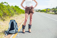 Backpacking woman on the roadside posing Royalty Free Stock Photography