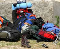 Backpacks bags and boots piled up after the long walk of the boy Royalty Free Stock Photos