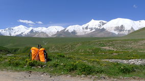 Backpacks and holy snow mountain Anymachen on Tibetan Plateau royalty free stock photography