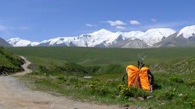 Backpacks and holy snow mountain Anymachen on Tibetan Plateau. Qinghai, China Stock Photo