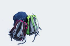 Backpacks in snow. Three hiking backpacks in snow. Adult and kids backpacks isolated on white background. Copy space. Family hiking on beautiful cold winter day Royalty Free Stock Photos