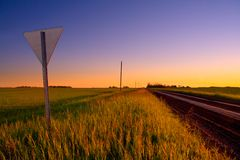 Backroad Yield. A yield sign marks a backroad intersection at sunset stock photos