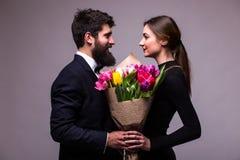 年轻家庭夫妇画象爱上花束的多色郁金香摆在灰色backround的经典衣裳穿戴了 库存图片